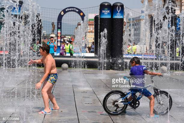 Children play in a fountain at the Uefa Super Cup fan zone in Skopje on August 7 2017 one day ahead of UEFA Super Cup match between Real Madrid and...