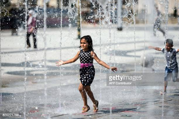 Children play in a fountain in Skopje on July 21 where temperatures reached 35 C / AFP PHOTO / Robert ATANASOVSKI
