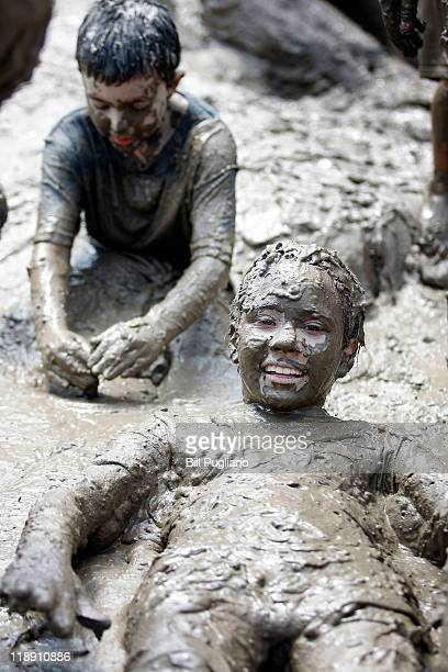 Children play in a giant lake of mud during Wayne County's 2011 Mud Day event at Nankin Mills Park July 12 2011 in Westland Michigan The annual event...