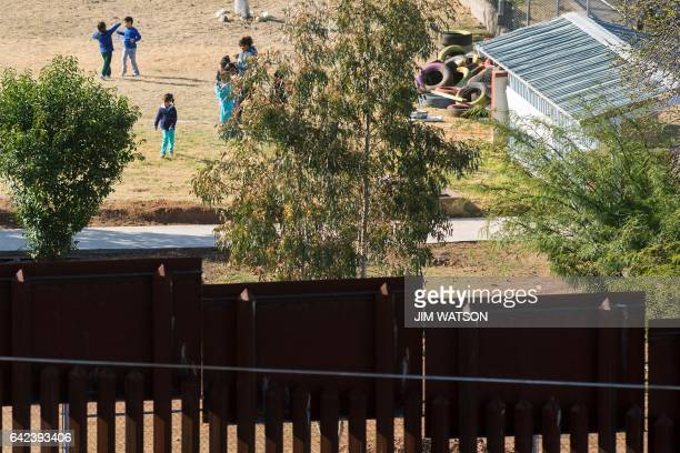 Children play in a playground on the Mexico side near a section of the border fence in Nogales Arizona on February 17 on the US/Mexico border this...