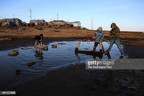 Children play in a puddle in the tiny bush village Hooper Bay AK which has a population of about 1000 people according to 2010 census data on May 14...