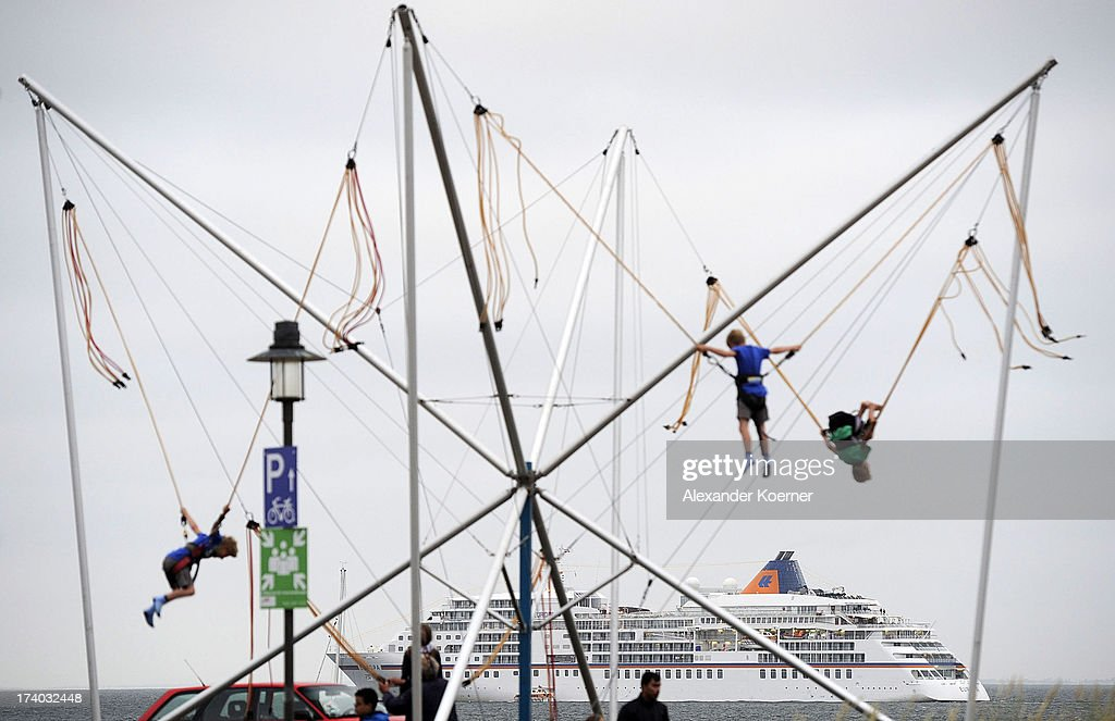 Children play in a rope course in front of the liner MS Europa in the List harbour on the island of Sylt on July 19, 2013 in List, Germany. The vessel invited German celebrities for a party this evening and will continue its journey toward Copenhagen after a 24-hour stop off the coast of List.