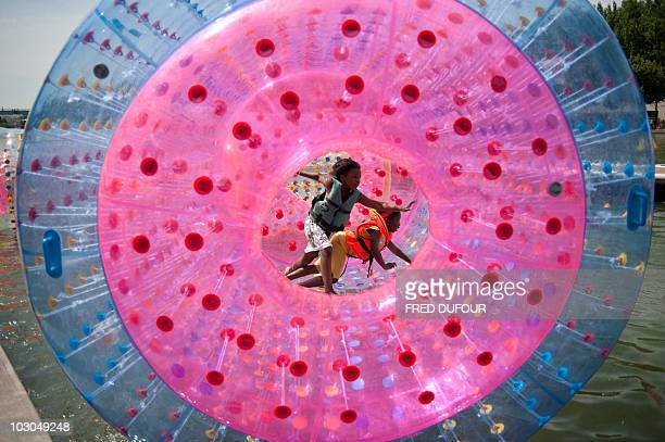 Children play in an unflatable boat on the opening day of 'Parisplage' event on July 20 2010 in Paris For the nineth summer Paris transforms the...