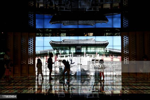 Children play in front of a screen showing South Korea's Bulguksa temple at Incheon International Airport in Incheon South Korea on Thursday Aug 8...