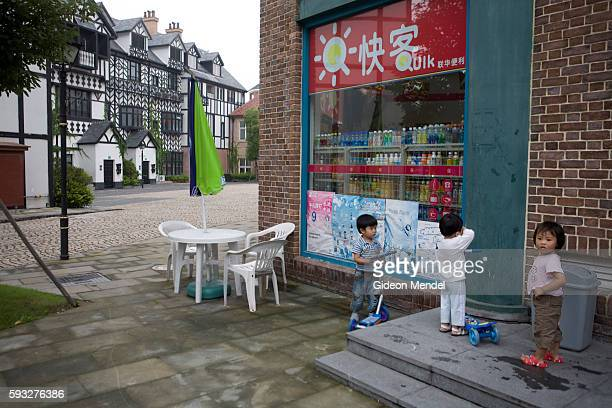 Children play in front of a Tudor style housing development in Thames Town an English village in China The architecture here imitates classic English...