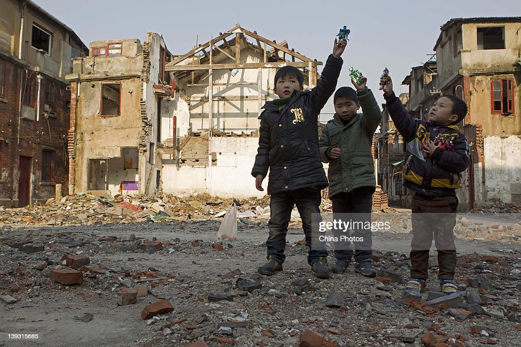 Children play in front of houses being demolished at the North Bund on February 19, 2012 in Shanghai, China. According to local media, the North Bund area will be reconstructed as a international shipping and financial zone, a modern commercial and high-end residential area, and recreation center.