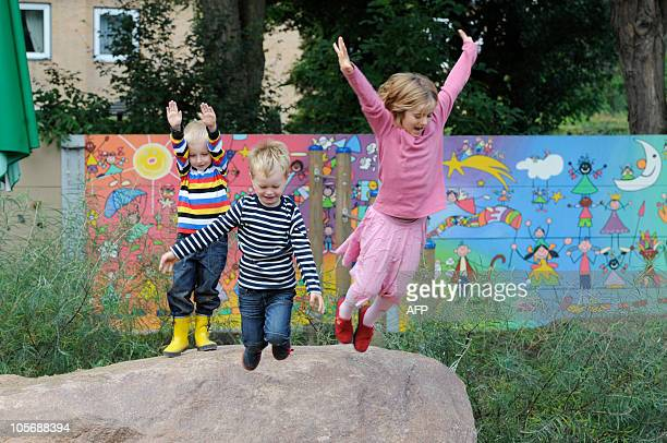 Children play in front of noise protection wall in a kintergarten in the northern German city of Hamburg on September 12 2010 The day care centre had...