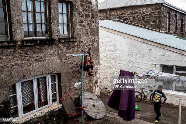 Children play in the backyard of Ladder's Hill fort houses on October 20 2017 in Saint Helena a British Overseas Territory in the South Atlantic...