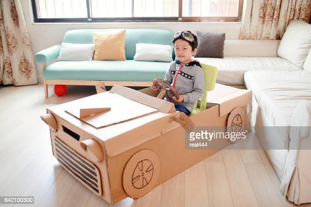 Children play in the cardboard car