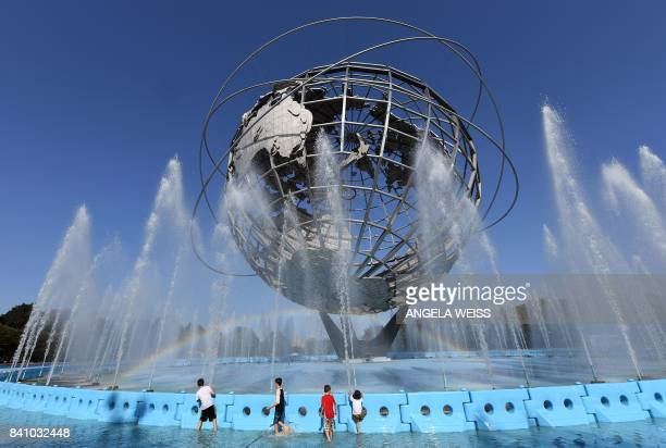 Children play in the fountain by the Unisphere steel structure at Flushing MeadowsCorona Park during the 2017 US Open at the USTA Billie Jean King...