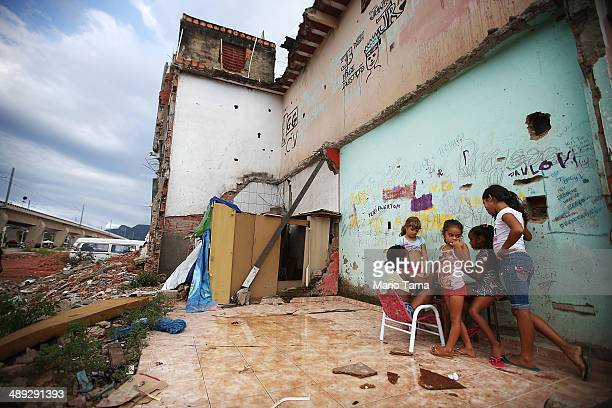 Children play in the rubble of a former home next to construction in the Manguinhos 'favela' on May 10 2014 in Rio de Janiero Brazil Residents from...
