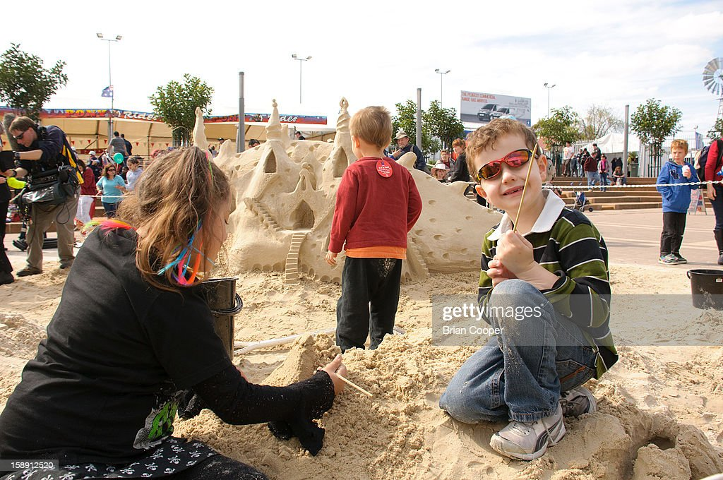 CONTENT] Children (a boy and a girl) play in the sand near a dragon themed sand castle at the Royal Adelaide Show.