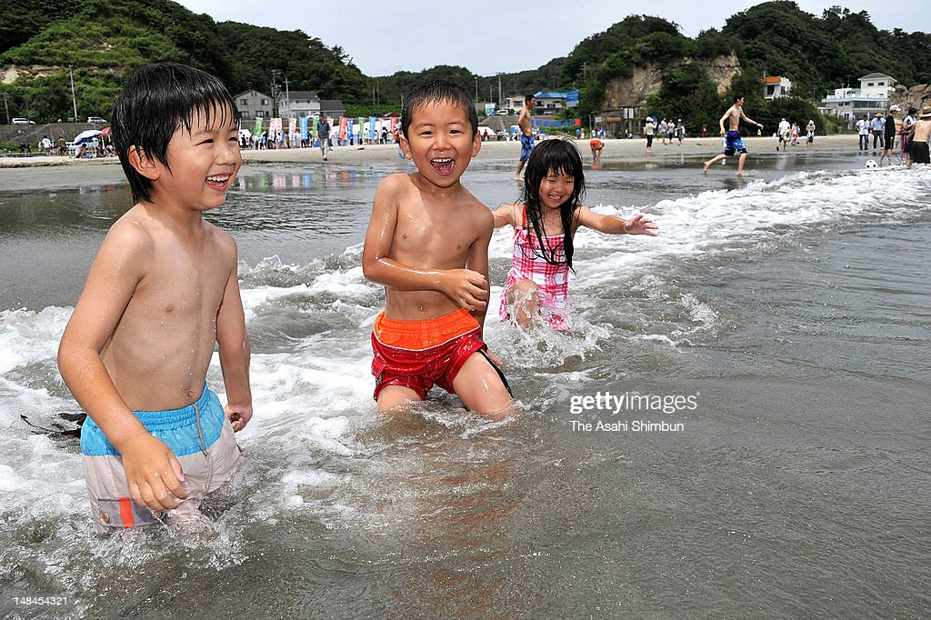 Children play in the sea at Nakoso Beach, opens for the first time after the Fukushima Daiichi Nuclear Power Plant accident on July 16, 2012 in Iwaki, Fukushima, Japan. No radioactive substance was detected but the local organisers will check the radiation level twice a day during the beach opening period.