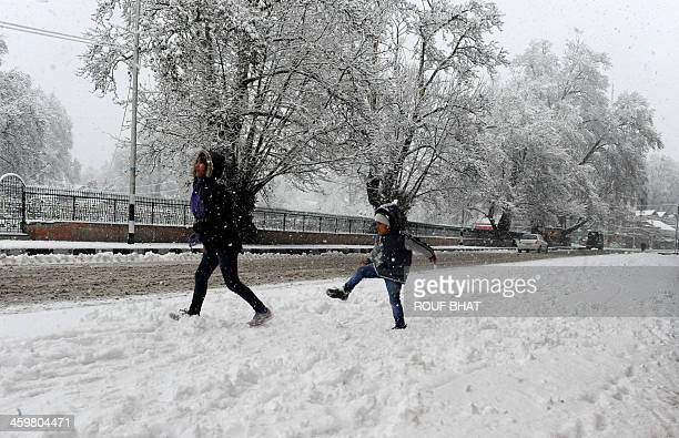 Children play in the snow during a snowfall in Srinagar on December 31 2013 A cold wave further tightened its grip in Jammu and Kashmir with most...