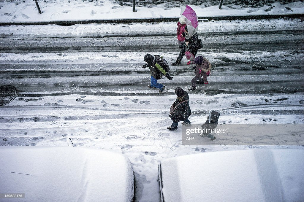Children play in the snow on their way to school on January 15, 2012 on a street of Lyon. AFP PHOTO / JEFF PACHOUD