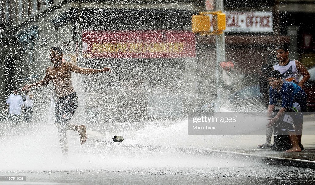 Children play in water sprayed from a fire hydrant on June 9, 2011 in the Bronx borough of New York City. An early summer heat wave has hit the city with temperatures forecast to hit in the high nineties this afternoon.