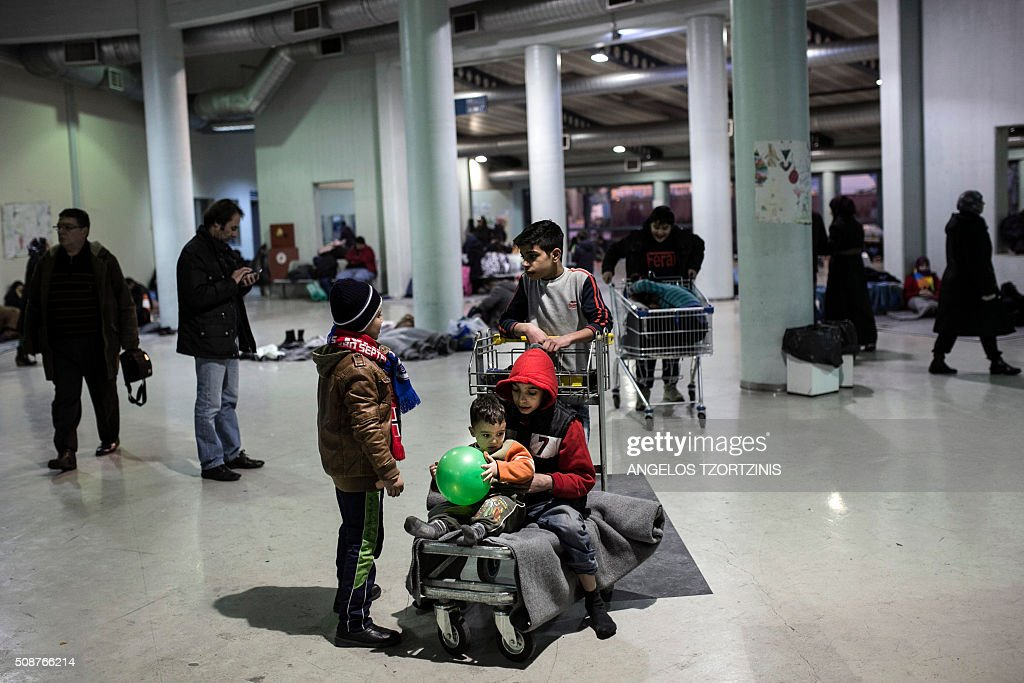 Children play inside a passenger terminal at the port of Piraeus near Athens on February 6, 2016. More than a million migrants landed in the 28-nation European Union last year, most of them crossing into Greece from Turkey, and then making their way through the Balkans to Germany and other northern member states. / AFP / ANGELOS TZORTZINIS