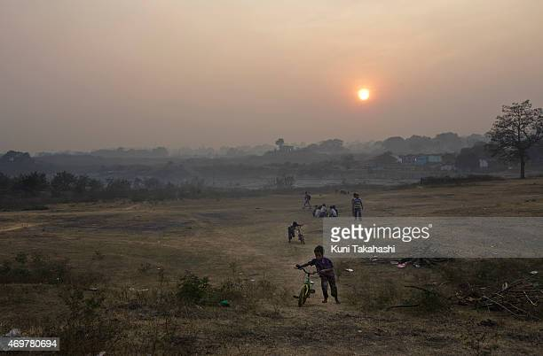 Children play near coal waste dumping site in Dhanbad Jharkhand India on December 5 2014 Indian government lead by Prime Minister Narendra Modi plans...