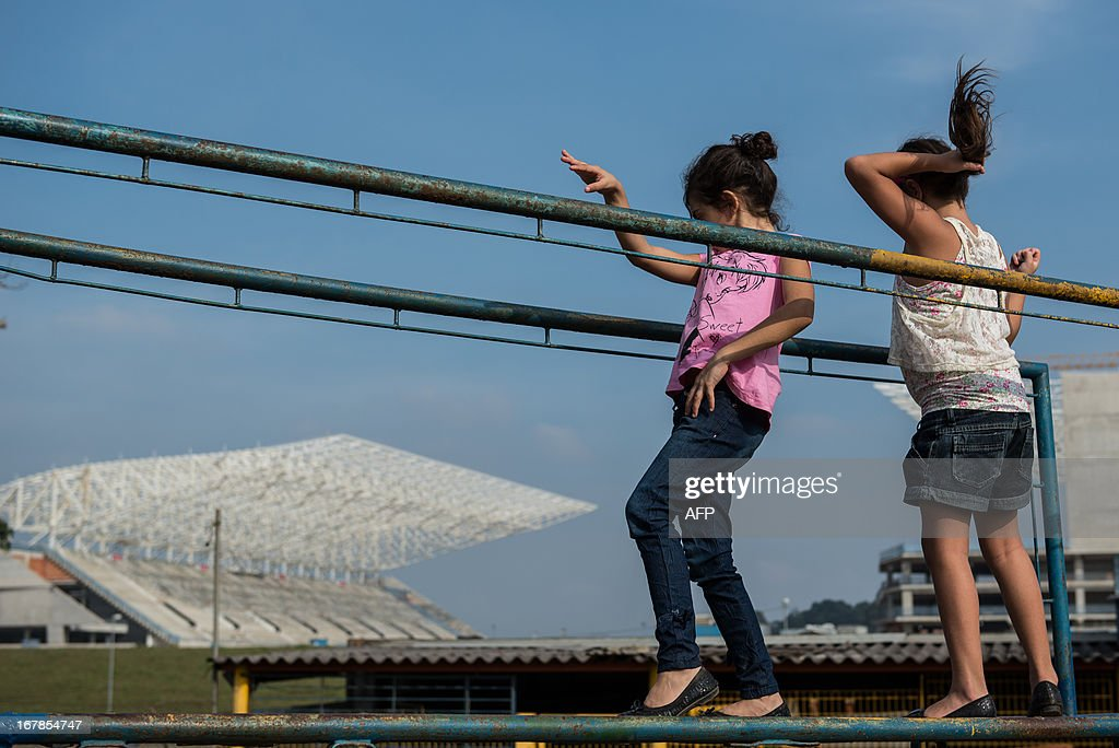 Children play near the Itaquerao Stadium (Corinthians Arena) in Sao Paulo, Brazil on May 1, 2013. The stadium has been completed 70 % of the process and will host the opening match of FIFA World Cup 2014. AFP PHOTO/Yasuyoshi CHIBA