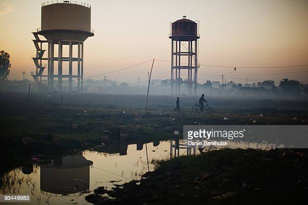 Children play near water towers in front of their homes near the Union Carbide factory on November 27 2009 in Bhopal India Twentyfive years after an...