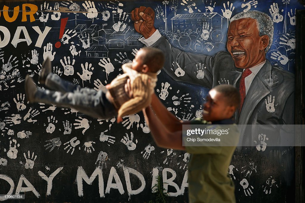 Children play next to a mural depicting former South African President Nelson Mandela near where he lived during the 1940s in Alexandra Township June 15, 2013 in Johannesburg, South Africa. A leader of the anti-apartheid movement and the first democratically elected president of South Africa, Mandela is spending an eighth night in hospital and is reported to be responding better to treatment for a recurring lung infection.
