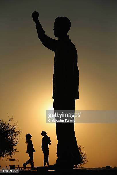 Children play next to a statue of Nelson Mandela which overlooks the city of Bloemfontein the birthplace of the ANC on July 12 2013 in Bloemfontein...