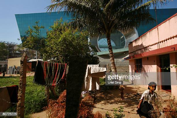 Children play next to their home as one of the Electronic city buildings is seen in the back on April 13 2008 in Bangalore India Many residents work...