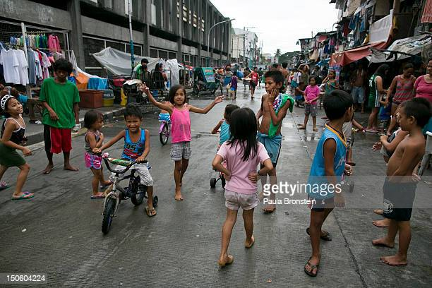 Children play on a congested street of slum dwellers in Binondo August 21 2012 in Manila Philippines Manila has a population of 20 million people...
