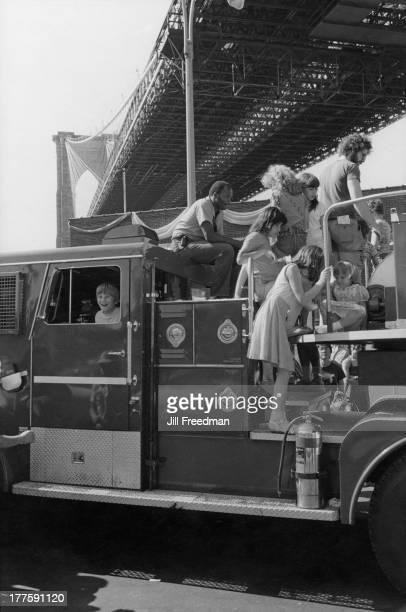 Children play on a fire engine underneath the Brooklyn Bridge New York City circa 1980
