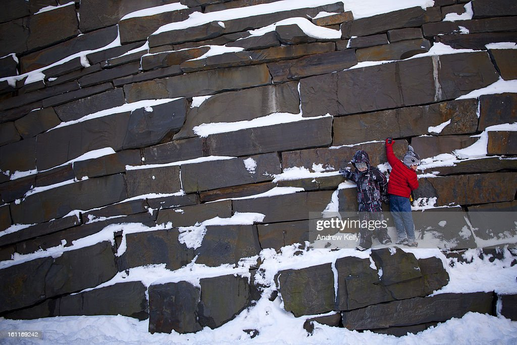 Children play on a rock wall covered in snow following a major winter storm on February 9, 2013 in New York City. New York City and much of the Northeast received a foot or more of snow overnight. Heavy snow warnings are in effect from New Jersey through southern Maine.