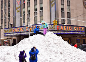 Children play on a snow pile outside Radio City Music Hall after a blizzard on January 24 2016 in New York City