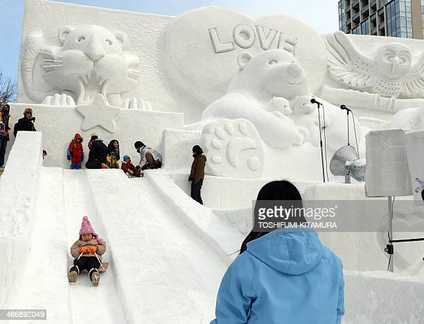 Children play on a snow slide during the 65th annual Sapporo Snow Festival on February 5 2014 The weeklong festival started with a total of 198 snow...