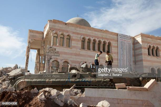 A'ZAZ ALEPPO SYRIA Children play on an armored vehicle near a damaged mosque in A'zaz Syria