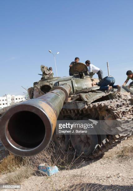 A'ZAZ ALEPPO SYRIA Children play on destroyed tanks in A'zaz Syria