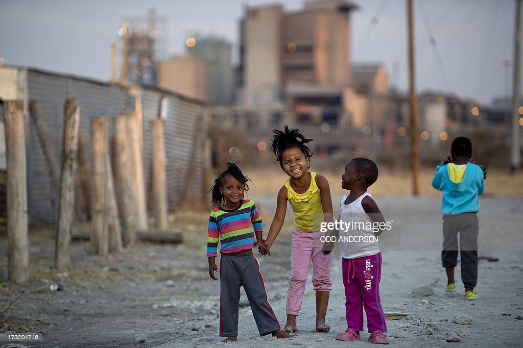 Children play on July 9, 2013 in the Nkaneng shantytown next to the platinum mine, run by British company Lonmin, in Marikana. On August 16, 2012, police at the Marikana mine open fire on striking workers, killing 34 and injuring 78, during a strike was for better wages and living conditions. Miners still live in dire conditions despite a small wage increase.