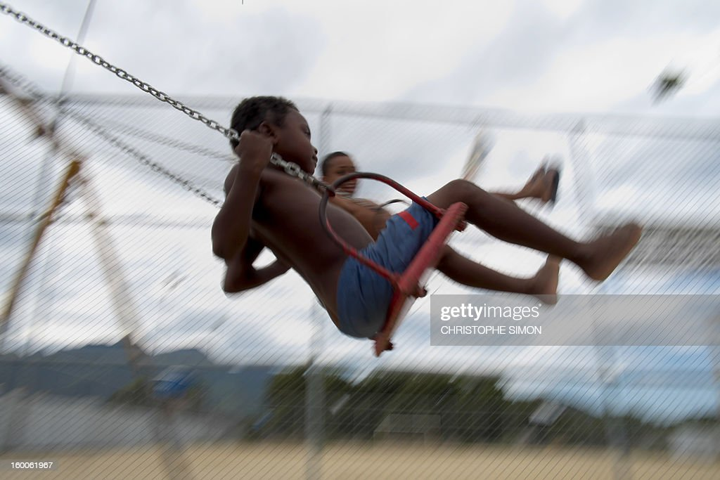 Children play on swings at Cidade de Deus slum in Rio de Janeiro, Brazil on January 25, 2013.
