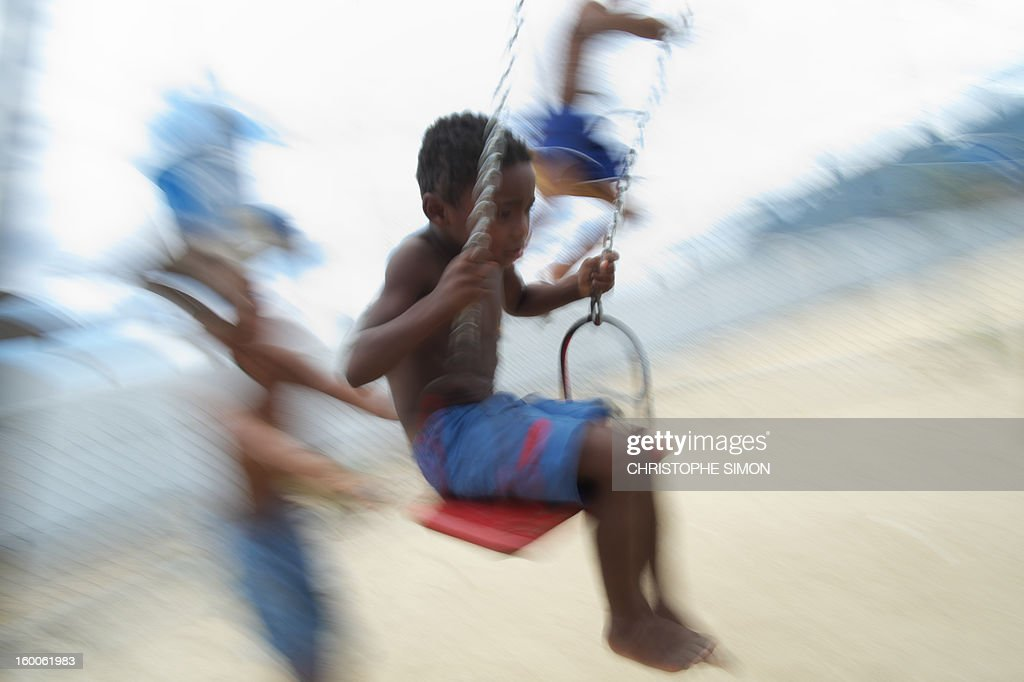 Children play on swings at Cidade de Deus slum in Rio de Janeiro, Brazil on January 25, 2013. AFP PHOTO / CHRISTOPHE SIMON