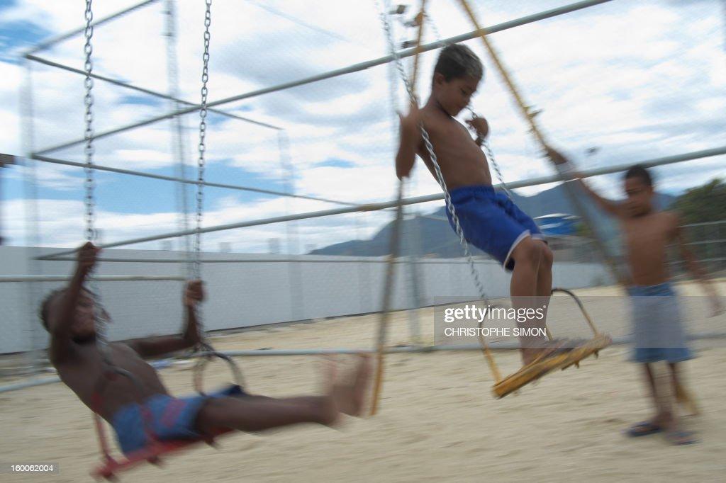 Children play on swings at Cidade de Deus slum in Rio de Janeiro, Brazil on January 25, 2013. AFP PHOTO / CHRISTOPHE SIMON