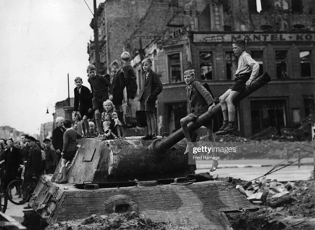 Children play on the bomb sites and wrecked tanks in Berlin, in the aftermath of the fighting in the city.