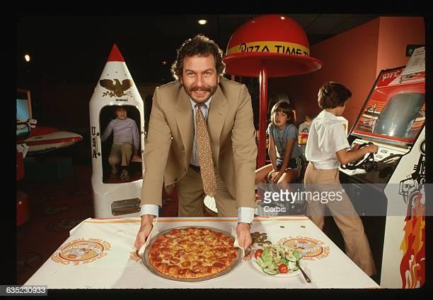 Children play on video games behind Nolan Bushnell at a restaurant