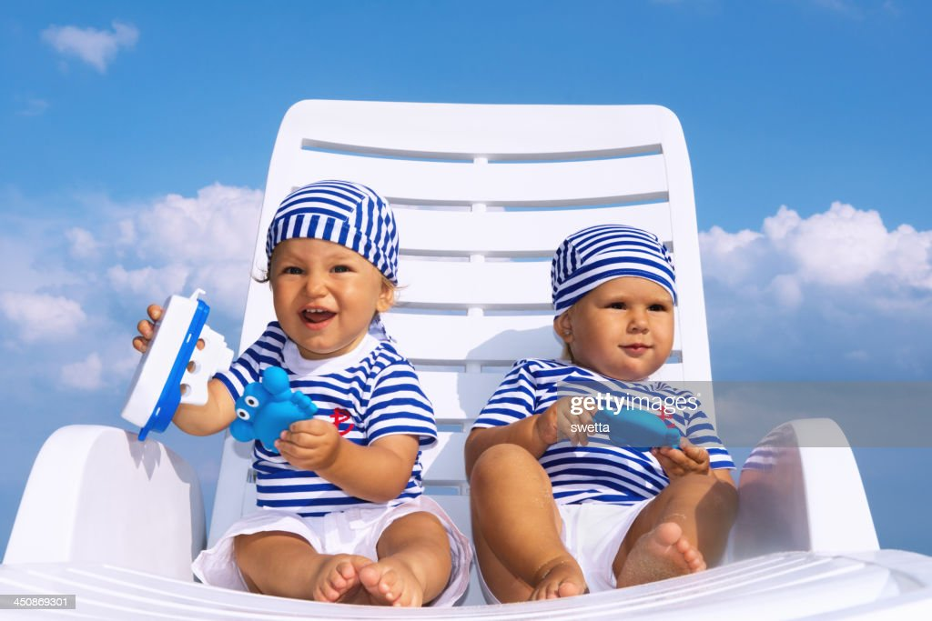 Babies play on white lounge chair : Stock Photo