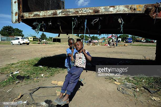 Children play oustide a tent used as a polling station on the eve in Mbare township on March 17 2013 Zimbabwe was tallying the ballots from a...