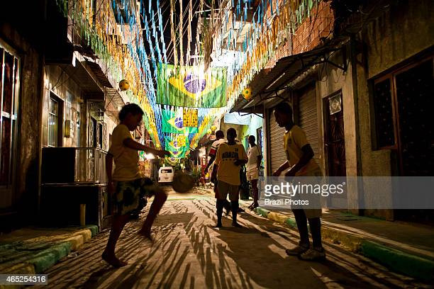 Children play soccer at night in Favela da Mare street decoration for the World Cup