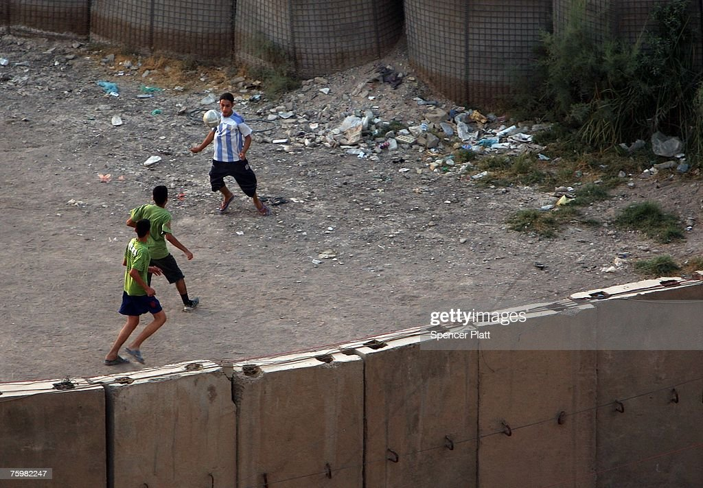 Children play soccer behind blast walls August 6, 2007 over Baghdad, Iraq. Twenty-eight people, including 19 children, were killed today when a suicide bomber detonated his bomb-laden truck in a residential area in the northern Iraqi city of Tal Afar.