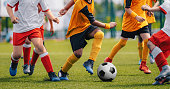 Children Play Soccer Game. Young Boys Running and Kicking Football Ball on Grass Sports Field