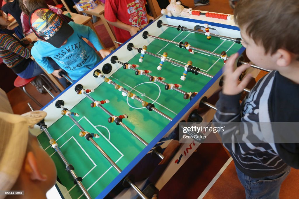 Children play table soccer at the 'Arche' youth center in Marzahn-Hellersdorf district on October 5, 2012 in Berlin, Germany. The Arche (which means Ark) is a Christian-based facility that provides children of all ages with a hot lunch, help with homework, arts and play facilities and in general a welcome place to come to in Marzahn-Hellersdorf district in east Berlin, a district with high levels of unemployment and social problems. An employee said up to 90% of the children come from challenged families and that many arrive at Arche illiterate.