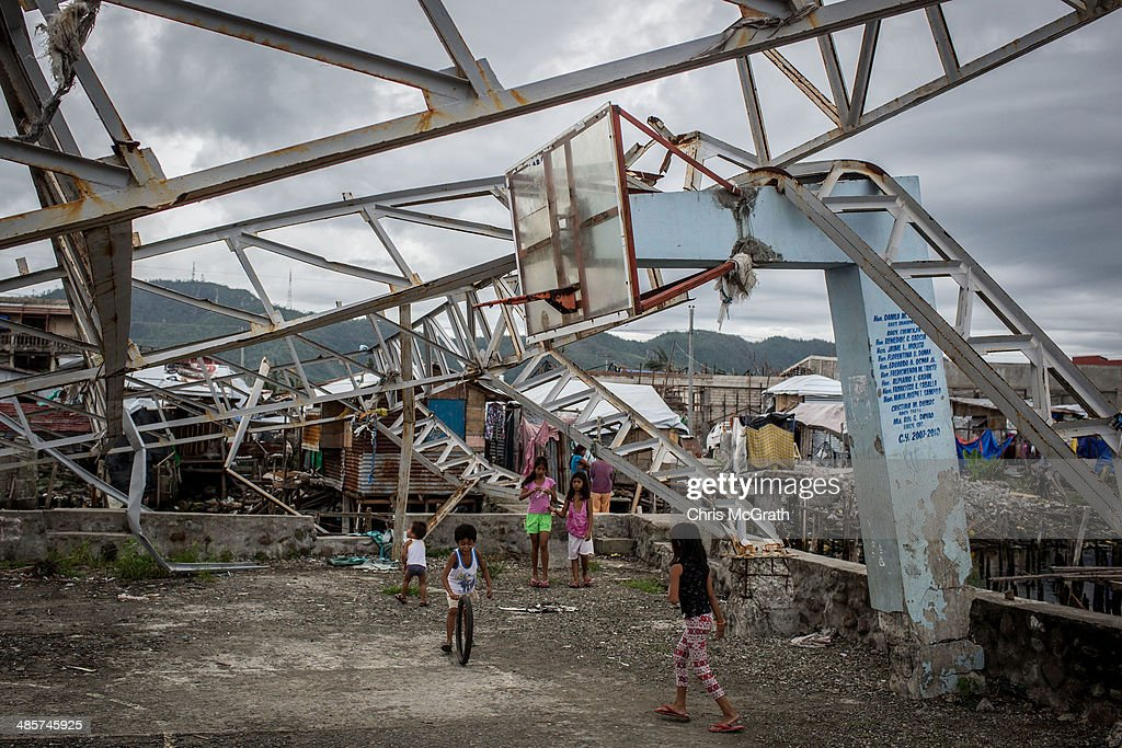 Children play under a damaged basketball hoop on April 20, 2014 in Tacloban, Leyte, Philippines. Basketball is the most popular sport in the Philippines. In the aftermath of Superstorm Yolanda that struck the coast on November 8, 2013 leaving more than 6000 dead and many more homeless, basketball hoops were some of the first things to be repaired and rebuilt amongst the rubble, showing the Filipino's resilience and intense love for the sport. Five months after the storm, basketball courts have re-emerged in large numbers across the damaged provinces using any available space and many being rebuilt from storm debris.