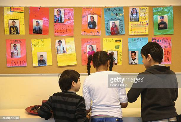 Children play under photographs of fellow pupils at the 'Welcome Class' for immigrant children including children of migrants and refugees at the...
