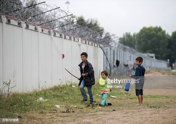 Children play under razor wire placed along the border at a informal camp besides the border fence close to the E75 Horgas border crossing between...