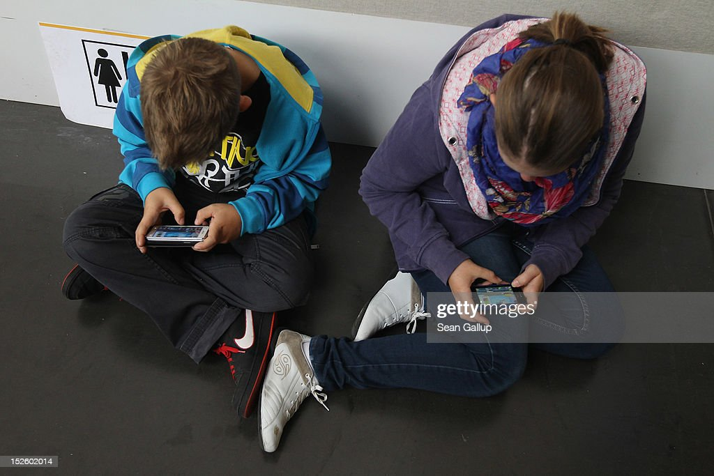 Children play video games on smartphones while attending a public event on September 22, 2012 in Ruesselsheim, Germany. Smartphones, with their access to social networks, high-resolution screens, video games and internet acess, have become commonplace among children and teenagers across the globe.